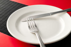 Empty plate with fork and knife Royalty Free Stock Image