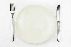 Empty plate with fork and knife Royalty Free Stock Images