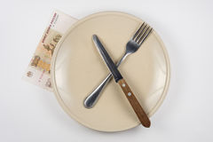 Empty plate with fork and knife, close is hundred-ruble note, white background Stock Photos