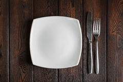 Empty plate, fork and knife on the dark wood background Stock Photography