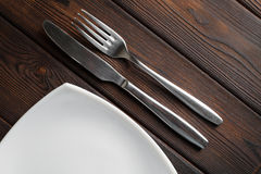 Empty plate, fork and knife on dark wood background Royalty Free Stock Photos
