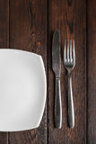 Empty plate, fork and knife on dark wood background Royalty Free Stock Photo