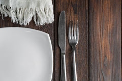 Empty plate, fork and knife on dark wood background Royalty Free Stock Image