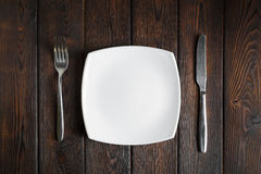 Empty plate, fork and knife on dark wood background Stock Photos