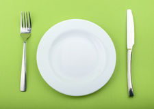 Empty plate, fork and knife on green background Stock Photos