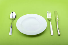 Empty plate, fork and knife on green background Stock Images