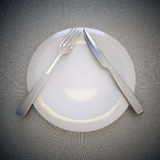 Empty plate, fork and knife. Royalty Free Stock Images