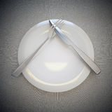 Empty plate, fork and knife. Empty plate, fork and knife on linen background Royalty Free Stock Photo