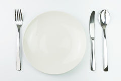 Empty plate with fork, knife and spoon Royalty Free Stock Images