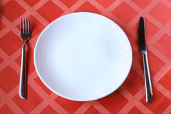 Empty plate with fork knife on table. Close up shot of an empty plate with fork knife on table Royalty Free Stock Photo