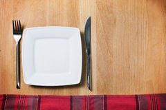 Empty plate with fork and knife, table arrangement Stock Images