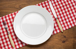 Empty plate with fork and knife on tablecloth over Royalty Free Stock Image