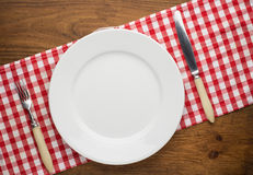Empty plate with fork and knife on tablecloth over. Wooden background Royalty Free Stock Photos