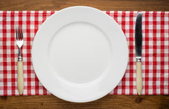 Empty plate with fork and knife on tablecloth over Stock Photo