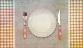Empty plate with fork and knife.Vintage retro style. Royalty Free Stock Photos
