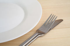 Empty plate with fork and knife on the wooden table Royalty Free Stock Photos