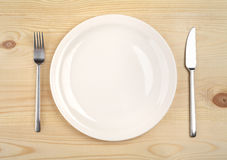 Empty plate with fork and knife on the wooden table.  Royalty Free Stock Images