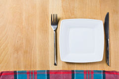 Empty plate with fork and knife on wooden table Royalty Free Stock Image