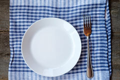Empty plate, fork and towel over wooden table background. Top View Royalty Free Stock Photo