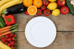 Empty plate framed with vegetables and fruits Stock Photos