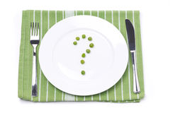 Empty plate with green peas in the shape of a question mark Royalty Free Stock Photography