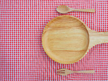 Empty plate with handle and spoons on red checked tablecloth Royalty Free Stock Image