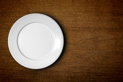 Empty plate. An image of an empty plate on a wooden background Stock Images