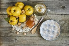 empty plate with jar of jam and quinces on rustic wooden background stock photography