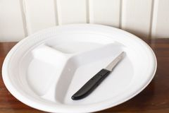 Empty Plate With Knife. Empty white styrofoam plate with a single paring knife stock images