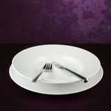 Empty plate with knife and fork Royalty Free Stock Images