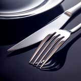 Empty plate with knife and fork on a black background.  royalty free stock photo