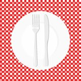 Empty plate with knife and fork. Dish fork and knife on a red tablecloth in a cage.  Stock Photo