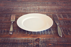 Empty plate with knife and fork on vintage wooden table Stock Photos
