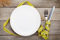 Empty plate with measure tape, knife and fork Stock Photo