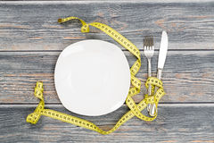 Empty plate with measure tape, knife and fork. stock photography