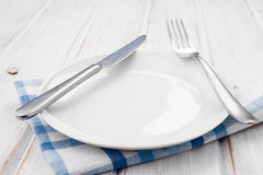 Empty plate and metal cutlery, on table Royalty Free Stock Photography