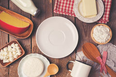 Empty plate with milk, cheese and butter on wooden background. View from above. Stock Image