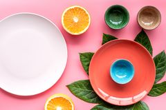 Empty plate mockup. Cups and plates near tropical leaves and fruits on pink background top view Stock Photos