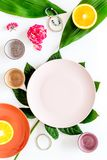 Empty plate mockup. Cups and plates near tropical leaves and fruits on white background top view Stock Images