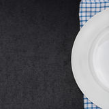 Empty plate on a napkin and black background for your text Royalty Free Stock Photography