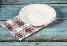 Empty plate with napkin on blue wooden table. Empty plate on tablecloth on wooden table Royalty Free Stock Image