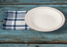 Empty plate with napkin on blue wooden table Stock Photography
