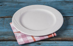 Empty plate with napkin on blue wooden table Royalty Free Stock Photos