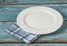 Empty plate with napkin on blue wooden table. Empty plate on tablecloth on wooden table Stock Photo