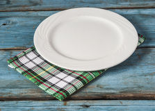Empty plate with napkin on blue wooden table. Empty plate on tablecloth on wooden table Royalty Free Stock Images