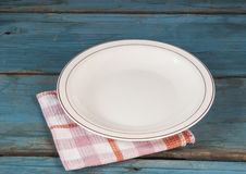 Empty plate with napkin on blue wooden table Royalty Free Stock Photography