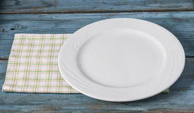 Empty plate with napkin on blue wooden table Royalty Free Stock Image
