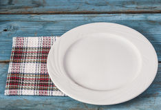 Empty plate with napkin on blue wooden table Stock Photos