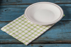 Empty plate with napkin on blue wooden table. Empty plate on tablecloth on wooden table Stock Photos