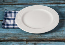 Empty plate with napkin on blue wooden table Royalty Free Stock Photo